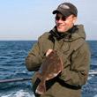 Angler im Kleinbott mit Scholle bei Langeland